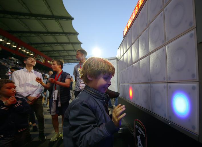 Jeune garçon jouant au mur digital dans les tribunes d'un stade
