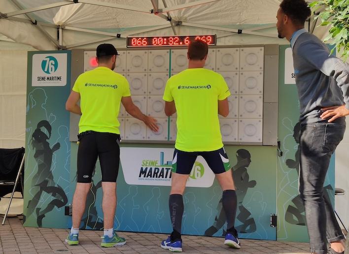 Groupe de deux participants au Seine Marathon jouant au mur digital