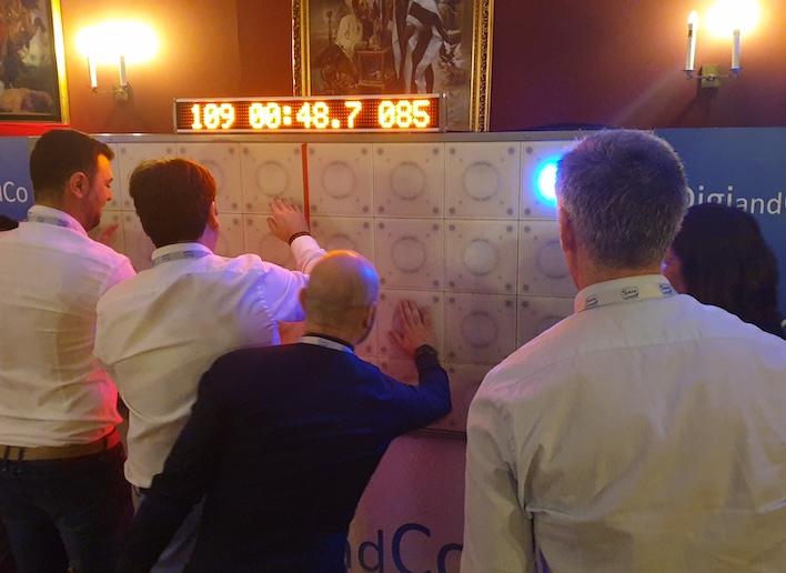 Trois collègues jouant au mur digital lors d'une soirée de séminaire