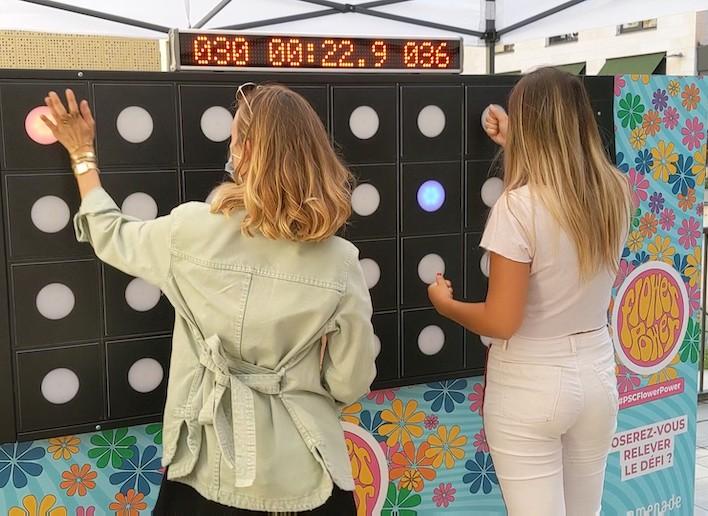 Deux femmes se défiant sur le mur digital au jeu de réflexe