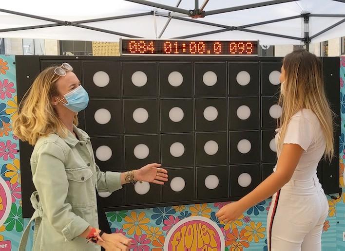 Deux femmes portant un masque jouant devant le mur digital