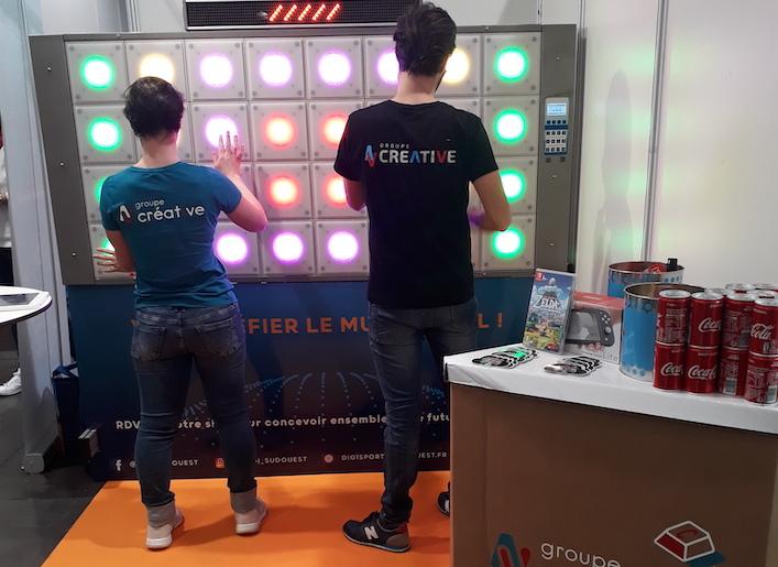 Deux personnes jouant au mur digital au jeu de réflexe lors d'un événement
