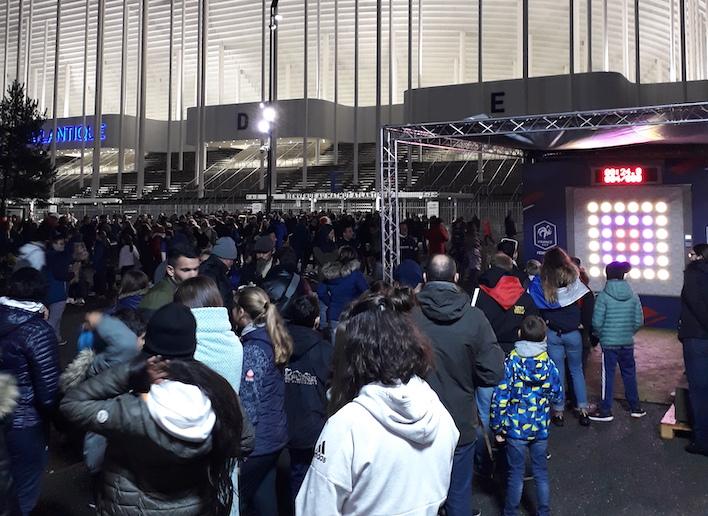 Groupe de spectateurs devant le mur digital à l'entrée du stade Matmut Atlantique