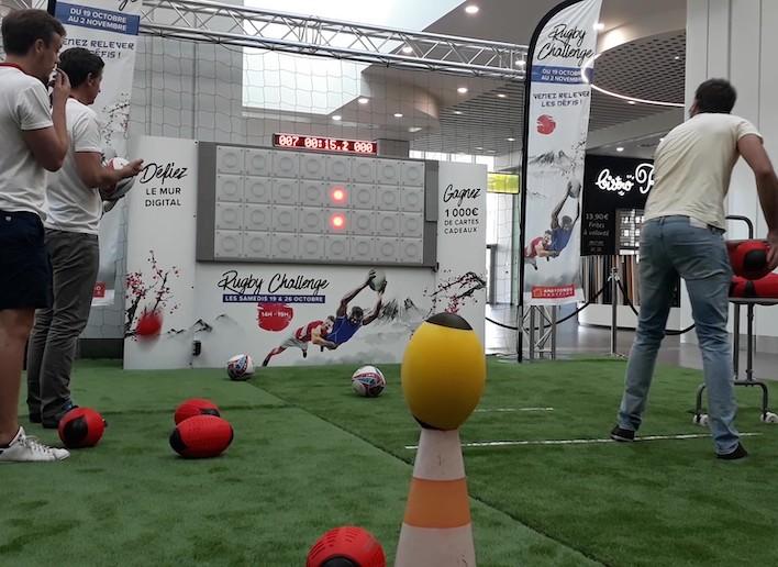 Homme jouant au rugby sur le mur digital en lançant un ballon