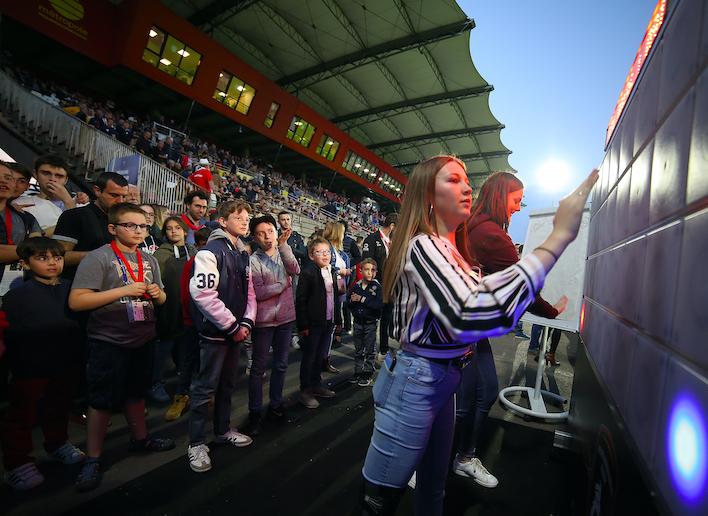 Deux jeunes filles jouant au mur digital dans les tribunes d'un stade