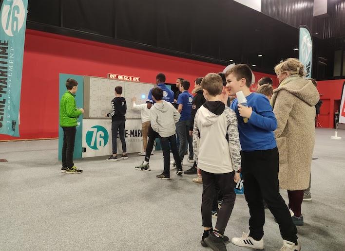 Jeunes enfants faisant la queue devant le mur digital pour y jouer