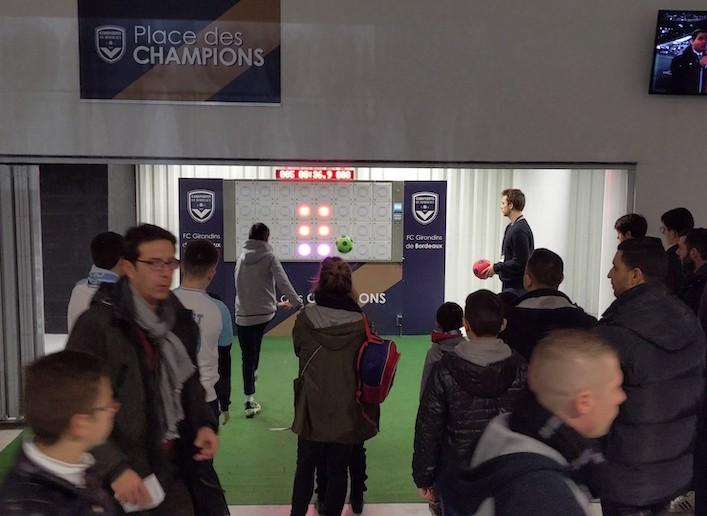 Groupe de spectateurs passant devant le mur digital dans les couloirs du stade des Girondins de Bordeaux