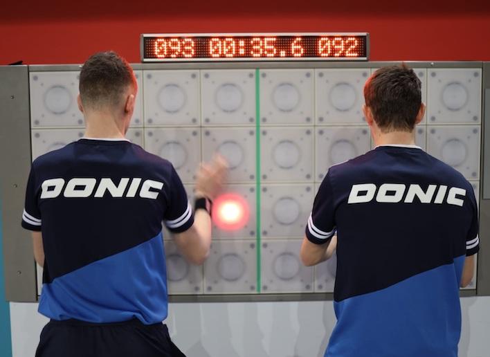 Duo de sportifs jouant au jeu de réflexe sur le mur digital