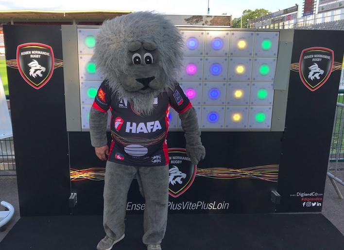 Mascotte du Rouen Normandie Rugby posant devant le mur digital