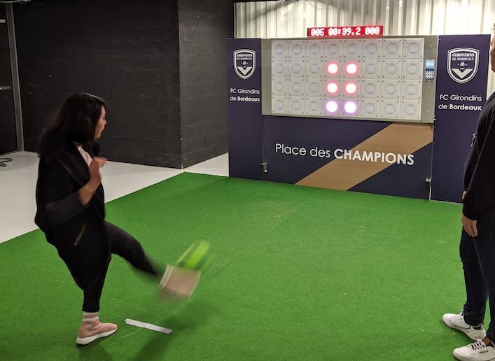 Jeune femme jouant au football sur le mur digital lors d'un match des Girondins de Bordeaux