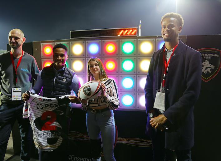 Quatre personnes posant devant de mur digital lors d'un match du Rouen Normandie Rugby