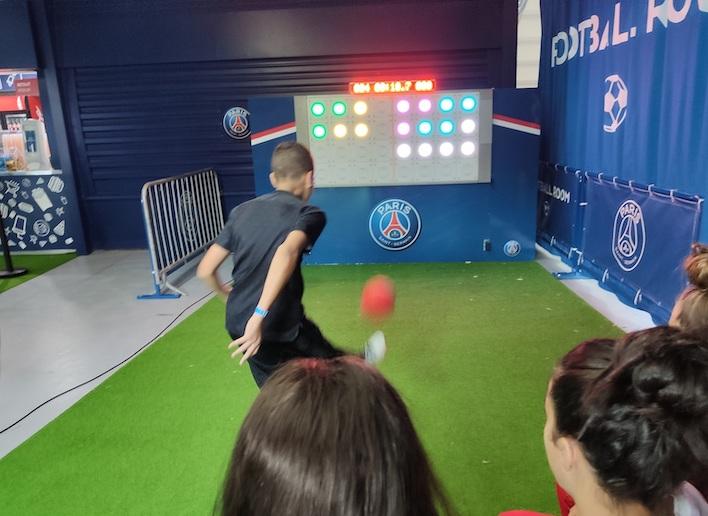 Garçon jouant au football face au mur digital lors d'un match du Paris Saint Germain