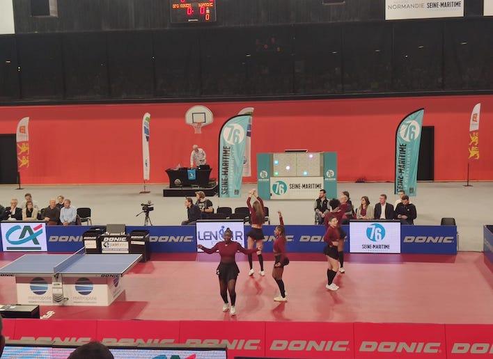 Groupe de danseuses dans un gymnase lors d'un match de tennis de table avec le mur digital en arrière plan