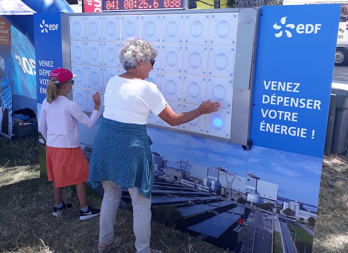 Une femme jouant au mur digital avec sa petite fille lors d'une animation EDF