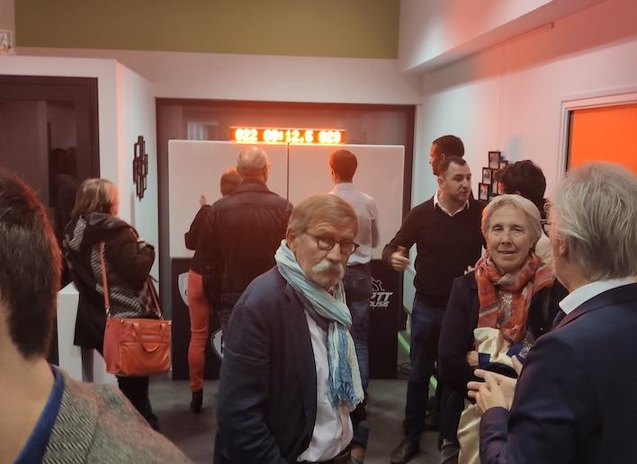 Groupe de personnes discutant devant le mur digital lors d'une fête