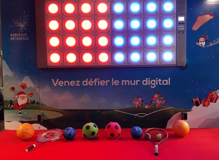 Ballons et Raquettes disposées devant le mur digital