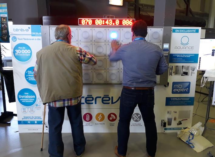 Deux personnes jouant au jeu de réflexe sur le mur digital