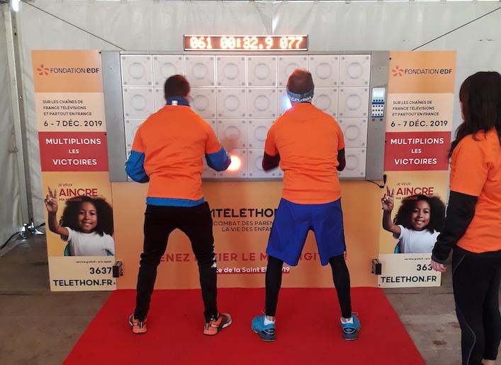 Deux hommes jouant au jeu de réflexe sur le mur digital lors d'un événement