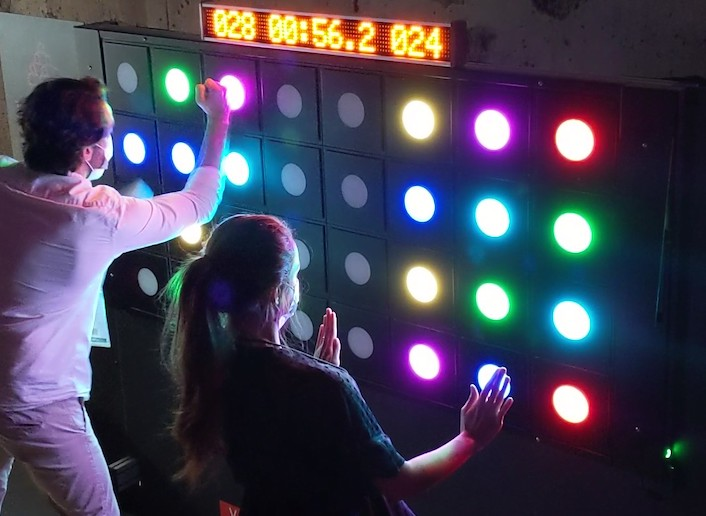 Deux joueurs face au mur digital testant leurs réflexes