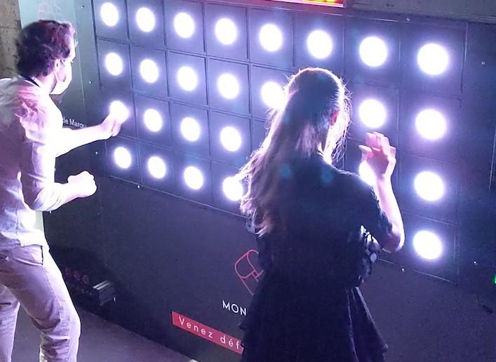 Deux personnes jouant au mur digital en duo lors d'une soirée