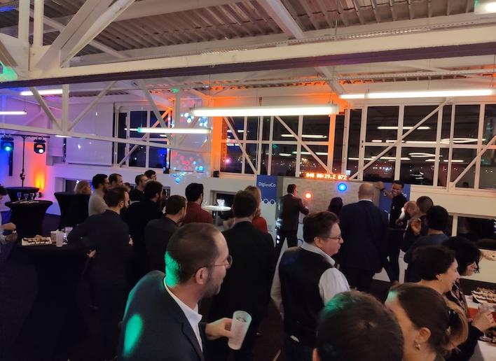 Salle de réception remplie de personnes dont deux jouant au mur digital