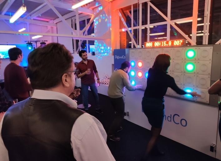 Deux personnes jouant en duo au mur digital lors d'une réception