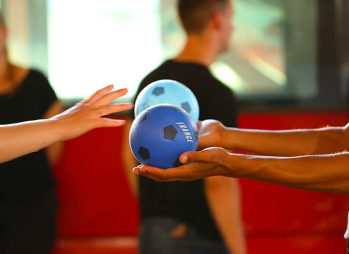 Main d'une personne qui tend un ballon bleu vers la main d'une autre personne