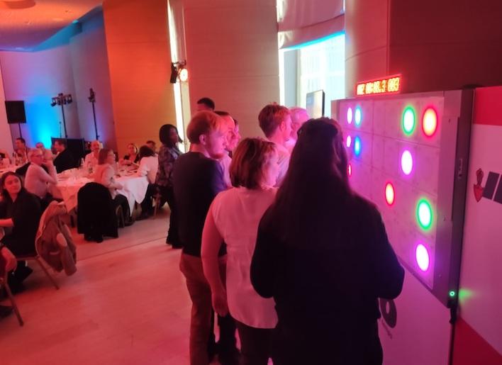 Groupe de personnes jouant au mur digital lors d'un dîner