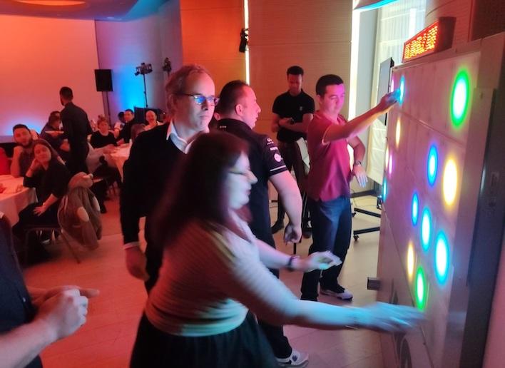 Groupe de personne jouant au mur digital lors d'une soirée