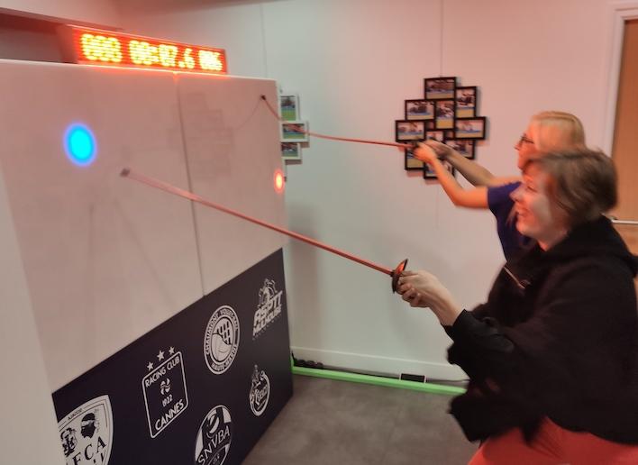 Groupe de deux personnes jouant à l'escrime sur le mur digital avec une épée